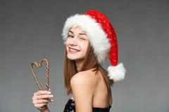 拿着在心脏形状的圣诞老人帽子的女孩圣诞节糖果 免版税库存照片