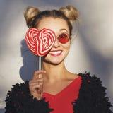拿着在心脏形状的女孩一个红色棒棒糖  库存照片