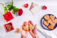 拿着在心脏形状的女性手自创曲奇饼充满爱的您词作为恋人的礼物在华伦泰` s天 白色木ta 免版税图库摄影