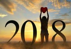 拿着在心脏形状的妇女气球在手上,当庆祝新年2018年时 库存图片