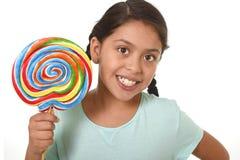 拿着在快乐的面孔表示的愉快的女孩大棒棒糖糖果在对甜概念的孩子爱 库存照片