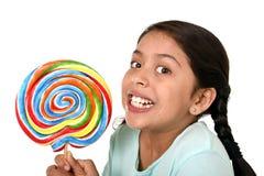 拿着在快乐的面孔表示的愉快的女孩大棒棒糖糖果在对甜概念的孩子爱 免版税库存图片