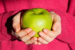 拿着在手上一个绿色苹果的女孩 免版税库存图片
