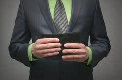 拿着在手上一个黑皮革钱包,照片的关闭的商人 免版税库存照片