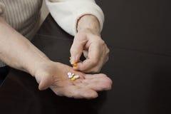 拿着在手上的一个老妇人的手片剂 免版税图库摄影