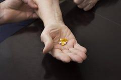 拿着在手上的一个老妇人的手片剂 免版税库存照片