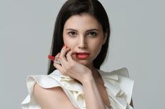 拿着在手指之间的一支唇膏妇女的画象 库存图片