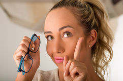 拿着在手指的隐形眼镜在她的面孔前面和拿着在她的其他手上每蓝色玻璃的年轻白肤金发的妇女  免版税图库摄影