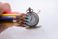 拿着在手表旁边的手颜色铅笔 免版税库存照片