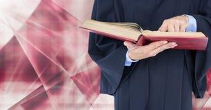 拿着在抽象形状前面的法官书 免版税库存照片