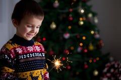 拿着在新的Year& x27的美丽的小孩灼烧的闪烁发光物; s Ev 图库摄影