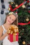 拿着在新年树前面的十几岁的女孩圣诞节礼物 免版税库存照片