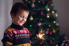 拿着在新年的Ev的美丽的小孩灼烧的闪烁发光物 免版税库存照片