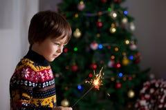 拿着在新年` s Ev的美丽的小孩灼烧的闪烁发光物 免版税图库摄影
