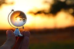 拿着在日落前面的男性手小水晶地球 库存照片