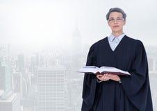 拿着在明亮的城市前面的法官书 免版税图库摄影