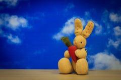 拿着在木的小的可爱的兔子一棵红萝卜与蓝天 免版税库存照片