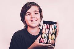 拿着在木箱的愉快的微笑的男孩点心macarons 库存照片