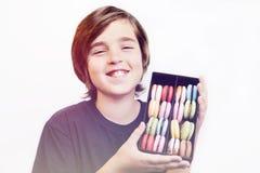 拿着在木箱的愉快的微笑的男孩点心macarons 免版税库存图片