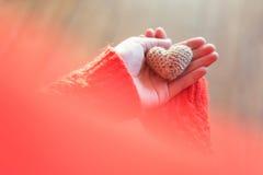 拿着在木背景的红色夹克的妇女小编织的心脏 爱和华伦泰` s天的概念 免版税图库摄影