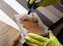 拿着在木表面的画家一把油漆刷 库存图片