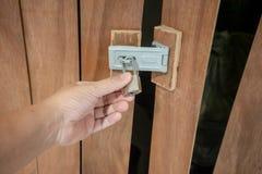 拿着在木门的人手锁着的挂锁 免版税库存图片