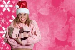 拿着在桃红色的圣诞老人帽子的俏丽的夫人giftboxes 库存图片