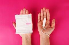 拿着在桃红色背景的妇女月经棉塞 月经时间 卫生学和保护 库存照片