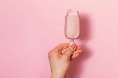 拿着在桃红色背景的少妇的手冰淇凌 Fashio 免版税库存照片