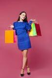拿着在桃红色背景的购物妇女购物袋l 免版税库存照片