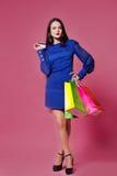 拿着在桃红色背景的购物妇女购物袋l 图库摄影