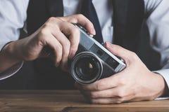拿着在桌上的一个人一台照相机 库存照片