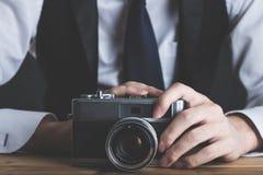 拿着在桌上的一个人一台照相机 免版税库存照片