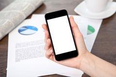 拿着在桌上的妇女手一个电话与图表 免版税库存照片
