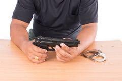 拿着在桌上的年轻人枪 库存图片