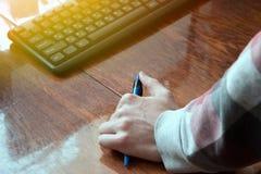 拿着在桌面上的把柄的手,键盘 图库摄影