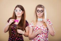 拿着在棍子的两名严肃的妇女狂欢节accessoies 免版税库存图片