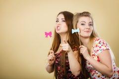 拿着在棍子的两名愉快的妇女狂欢节accessoies 免版税库存图片