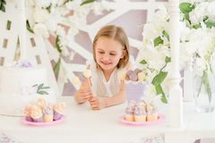 拿着在棒棒糖的小女孩五颜六色的甜棒棒糖 免版税库存图片