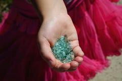 拿着在棕榈的小女孩玻璃小卵石 库存照片
