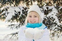 拿着在棕榈的美丽的白肤金发的微笑的女孩雪 免版税库存图片
