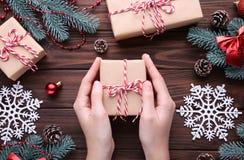 拿着在棕色木桌上的女性手礼物盒 免版税库存图片