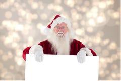 拿着在模糊的背景设计的圣诞老人广告牌 图库摄影