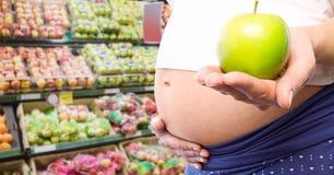 拿着在模糊的菜走道的孕妇中间部分苹果 免版税图库摄影