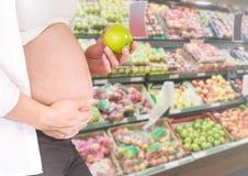拿着在模糊的菜走道的孕妇中间部分苹果 免版税库存照片