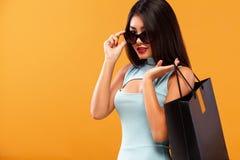 拿着在橙色背景的购物的愉快的亚裔妇女袋子黑星期五假日 复制空间待售广告 库存照片