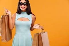拿着在橙色背景的购物的愉快的亚裔妇女袋子黑星期五假日 复制空间待售 免版税图库摄影