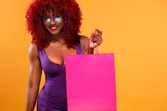 拿着在橙色背景的购物的美国黑人的妇女桃红色袋子黑星期五假日 复制空间为 库存照片