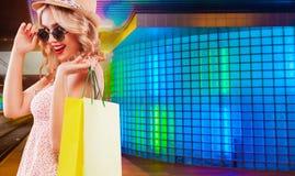 拿着在橙色背景的购物的美国黑人的妇女桃红色袋子黑星期五假日 复制空间为 免版税图库摄影