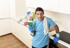 拿着在橡胶手套微笑的年轻愉快的人洗涤的洗涤剂浪花瓶 免版税图库摄影